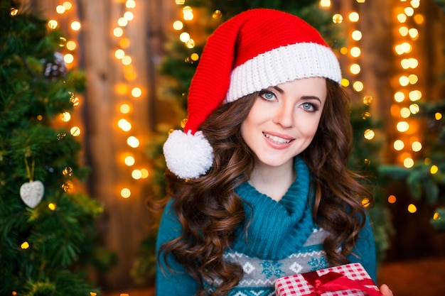 Lächelnde junge frau in santa helferhut mit geschenk roter box auf hintergrundweihnachtsbaum.