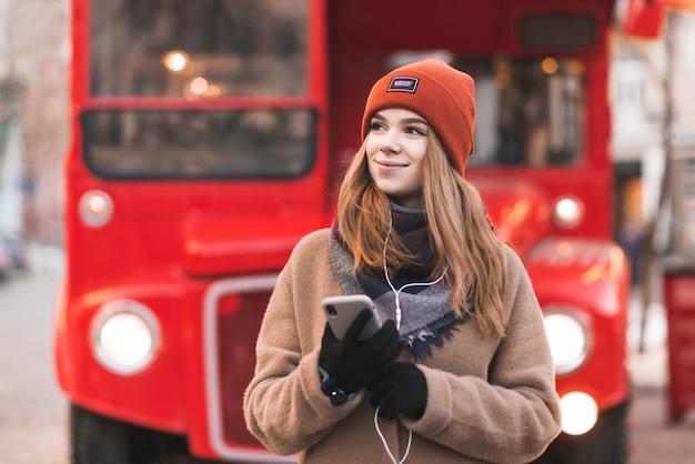 Lächelnde junge frau in warmer kleidung und einem smartphone in ihren händen hört musik in den kopfhörern und schaut seitwärts auf den hintergrund eines touristischen roten busses