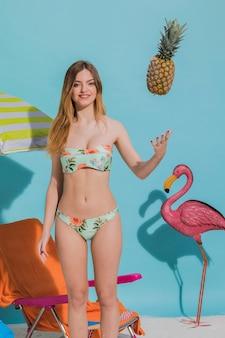 Lächelnde junge frau in werfender ananas des bikinis im studio