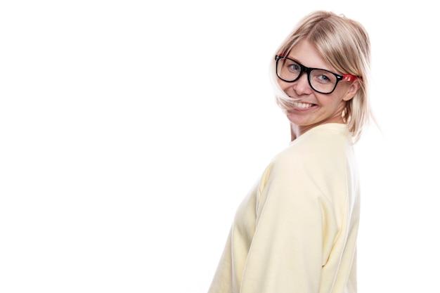 Lächelnde junge frau mit brille. hübsche blondine in einem gelben pullover. erfolg, glück und freiheit. isoliert auf weißem hintergrund. platz für text.
