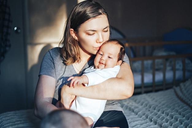 Lächelnde junge frau mit buch und baby auf einem bett