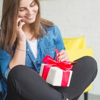 Lächelnde junge frau mit dem geburtstagsgeschenk, das auf mobiltelefon spricht