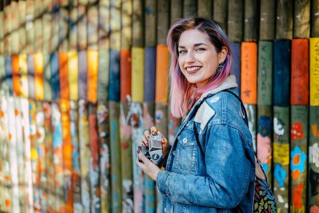 Lächelnde junge frau mit dem gefärbten haar, das kamera nahe der handgemalten wand hält lächelnde junge frau mit dem gefärbten haar, das kamera nahe der handgemalten wand draußen hält.