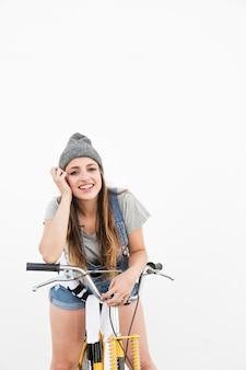Lächelnde junge frau mit dem gelben fahrrad, das kamera betrachtet