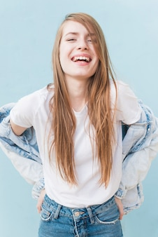 Lächelnde junge frau mit dem langen blonden haar, das auf blauem hintergrund steht