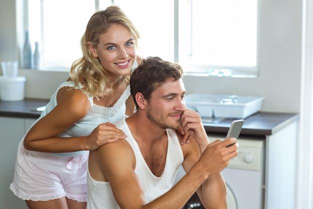 Lächelnde junge frau mit dem mann, der handy in der küche verwendet
