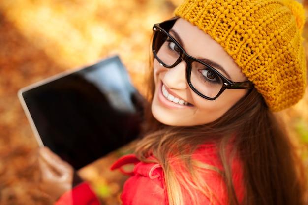 Lächelnde junge frau mit digitaler tablette