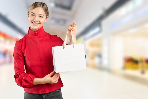 Lächelnde junge frau mit einkaufstaschen über mallhintergrund