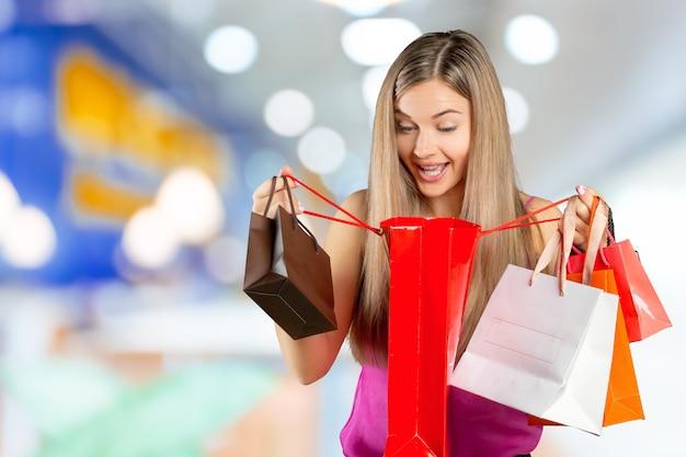 Lächelnde junge frau mit einkaufstüten über einkaufszentrum