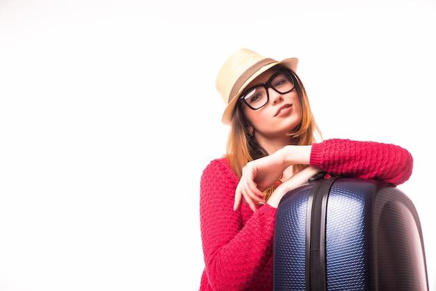 Lächelnde junge frau mit gefalteten händen auf koffer, der hut trägt. reisekonzept.