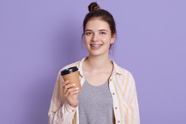Lächelnde junge frau mit haarknoten halten kaffee in händen wegnehmen