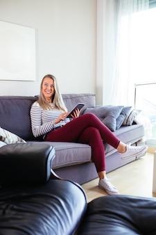Lächelnde junge frau mit ihrem tablet auf dem sofa in ihrem haus sitzend