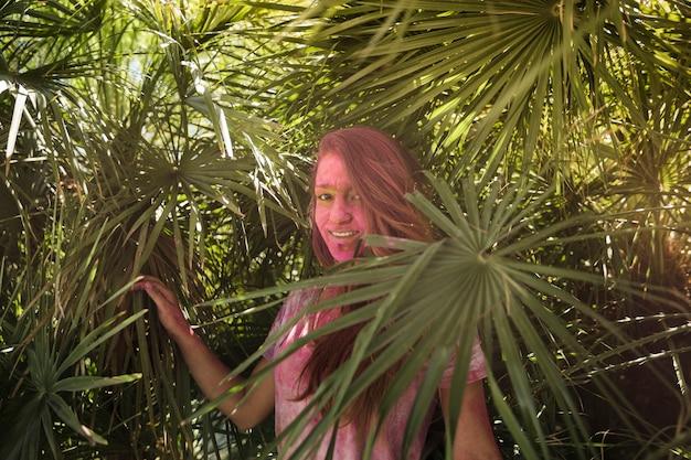 Lächelnde junge frau mit ihrer gesichtsbedeckung in holi farbe, die nahe den palmblättern steht
