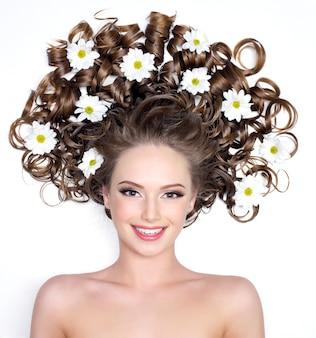 Lächelnde junge frau mit kamimilen in ihrem herrlichen langen haar auf weiß