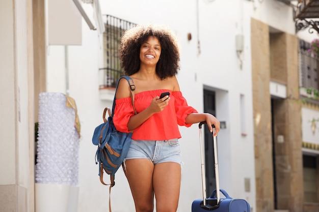 Lächelnde junge frau mit koffer und handy