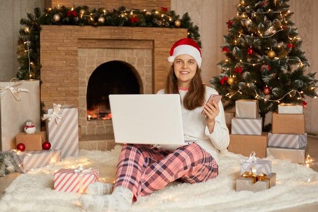 Lächelnde junge frau mit laptop, der in der nähe von weihnachtsbaum und geschenkboxen sitzt, silvester online arbeitet, hält smartphone in händen, trägt karierte hosen, hemd und weihnachtsmannhut.