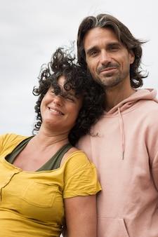 Lächelnde junge frau mit lockigem haar und gelben hemden stützt sich auf großen hübschen freund mit langen haaren.