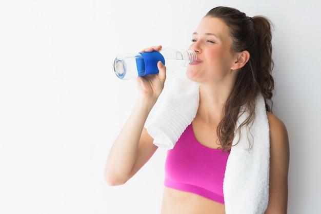 Lächelnde junge frau mit trinkwasser des tuches