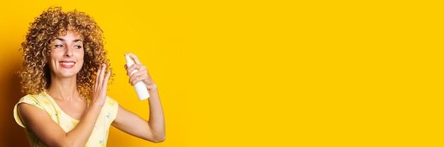 Lächelnde junge frau sprüht mit spray auf gelbem hintergrund. haar styling.