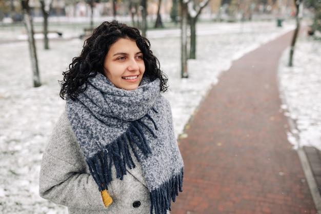 Lächelnde junge frau steht in einem frostigen verschneiten winterpark.