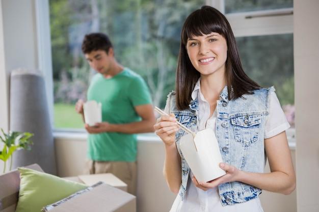 Lächelnde junge frau und fleisch fressende nudeln zu hause