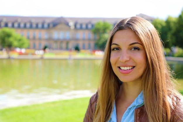 Lächelnde junge frau vor dem neuen schloss, stuttgart, deutschland