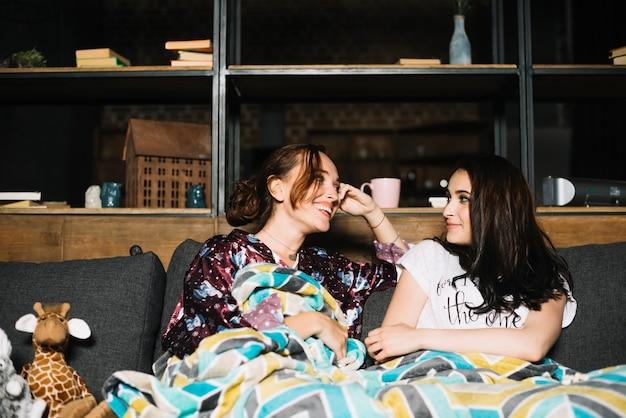 Lächelnde junge frauen, die auf dem sofa einander betrachtet sitzen
