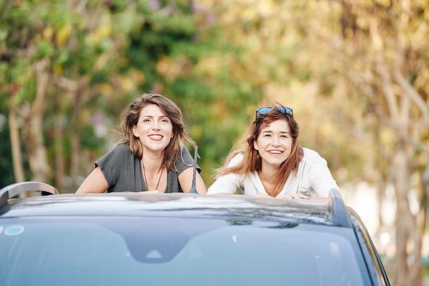 Lächelnde junge frauen, die im autokofferraum stehen