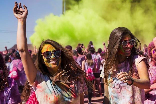 Lächelnde junge frauen, die in das holi festival tanzen