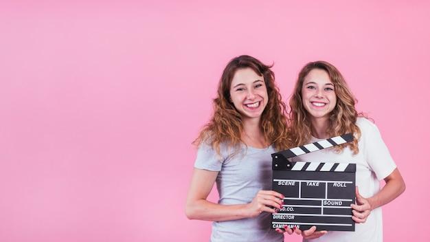 Lächelnde junge frauen, die scharnierventilbrett in den händen gegen rosa hintergrund halten