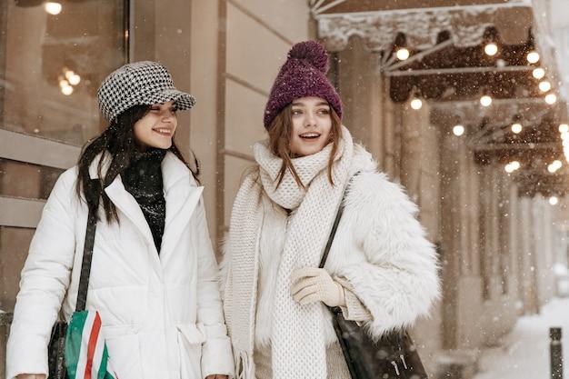 Lächelnde junge frauen, die warme winterkleidung plaudern