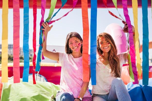 Lächelnde junge frauen mit holi farbe auf ihrem gesicht, das kamera betrachtet