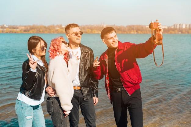 Lächelnde junge freunde, die gesichter beim nehmen von selfie machen