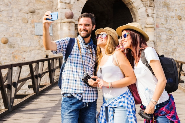 Lächelnde junge freunde, die selfie auf mobiltelefon nehmen