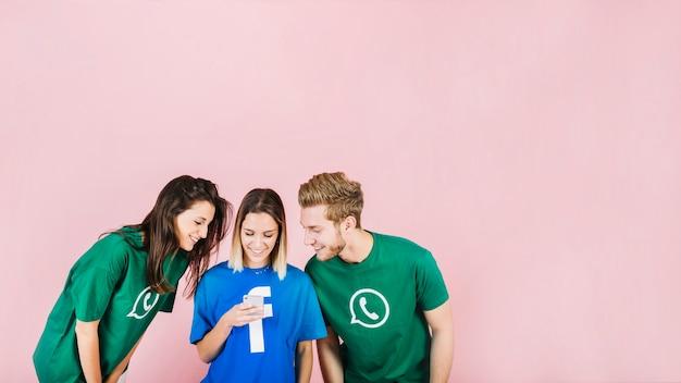Lächelnde junge freunde, die smartphone gegen rosa hintergrund betrachten