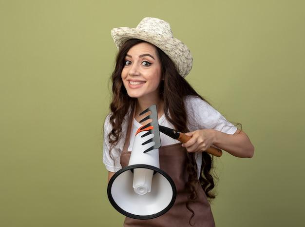 Lächelnde junge gärtnerin in uniform, die gartenhut trägt, hält rechen und lautsprecher lokalisiert auf olivgrüner wand
