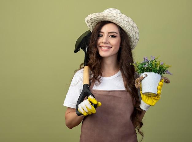 Lächelnde junge gärtnerin in uniform, die gartenhut und handschuhe trägt, hält blumentopf und spaten auf schulter isoliert auf olivgrüner wand mit kopienraum