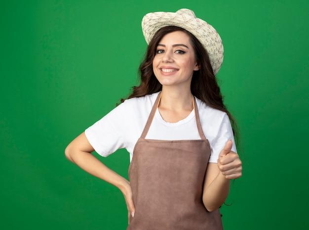 Lächelnde junge gärtnerin in uniform mit gartenhut daumen hoch isoliert auf grüner wand