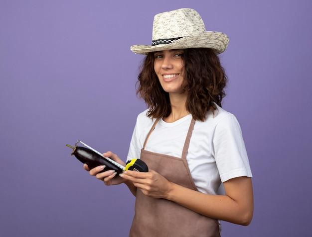 Lächelnde junge gärtnerin in uniform mit gartenhut, die auberginen mit maßband misst