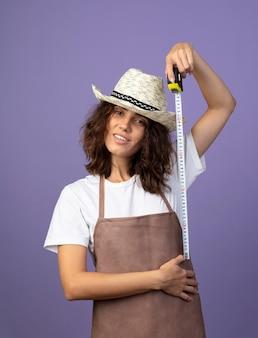 Lächelnde junge gärtnerin in uniform mit gartenhut, die sich mit maßband misst