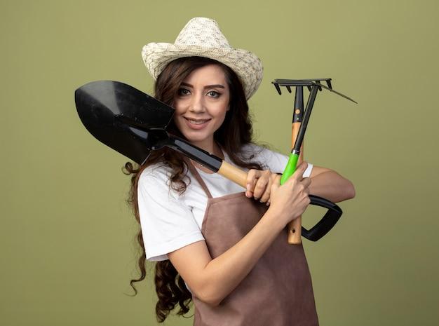 Lächelnde junge gärtnerin in uniform mit gartenhut hält gartengeräte isoliert auf olivgrüner wand