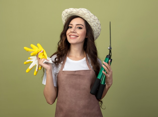Lächelnde junge gärtnerin in uniform mit gartenhut hält gartenschere und handschuhe isoliert auf olivgrüner wand