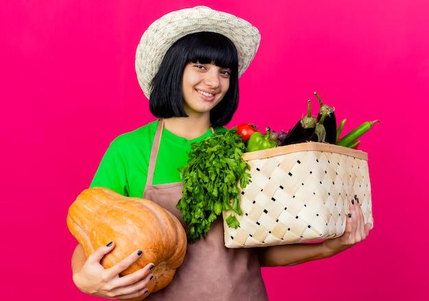 Lächelnde junge gärtnerin in uniform mit gartenhut hält gemüsekorb und kürbis suchen