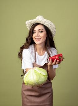 Lächelnde junge gärtnerin in uniform mit gartenhut hält kohl und paprika isoliert auf olivgrüner wand