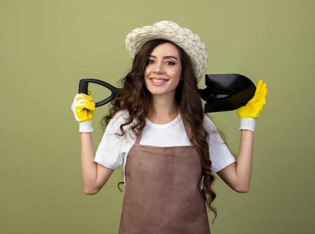 Lächelnde junge gärtnerin in uniform mit gartenhut und handschuhen hält spaten hinter dem hals isoliert auf olivgrüner wand
