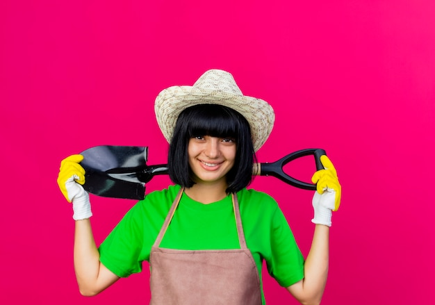 Lächelnde junge gärtnerin in uniform mit gartenhut und handschuhen hält spaten hinter dem hals