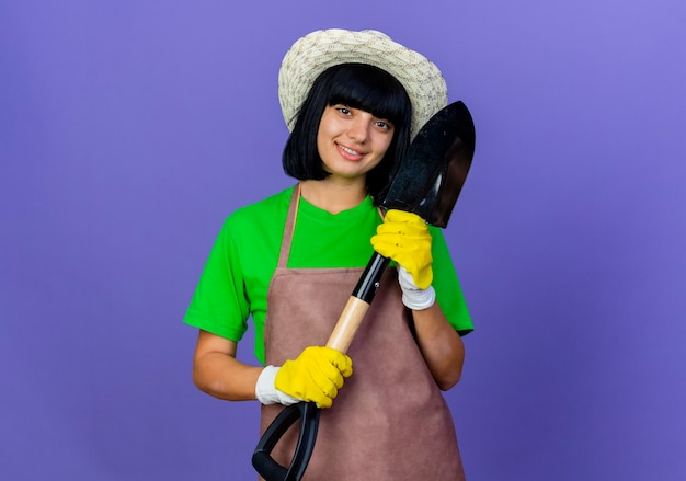 Lächelnde junge gärtnerin in uniform mit gartenhut und handschuhen hält spaten