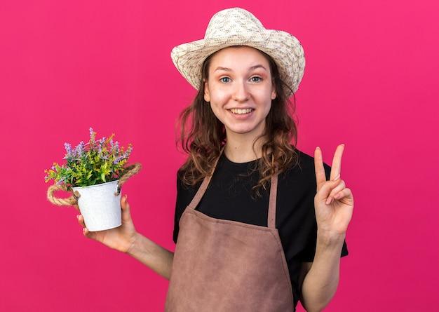 Lächelnde junge gärtnerin mit gartenhut, die blume im blumentopf hält und friedensgeste zeigt