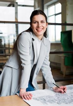 Lächelnde junge geschäftsfrau, die an blaupause arbeitet