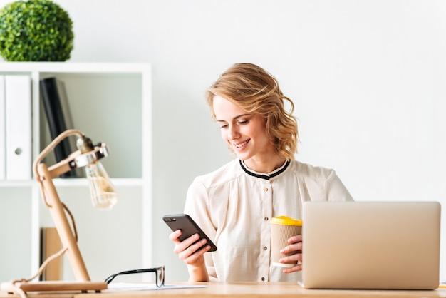 Lächelnde junge geschäftsfrau, die durch handy trinkt, das kaffee trinkt.